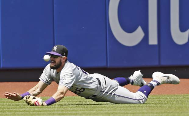 Colorado Rockies center fielder David Dahl (26) dives for J.D. Davis's run-scoring triple during the sixth inning of a baseball game against the New York Mets, Sunday, June 9, 2019, in New York. (AP Photo/Kathy Willens)