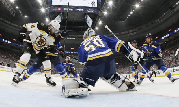 St. Louis Blues goaltender Jordan Binnington (50) catches the puck as Boston Bruins left wing Jake DeBrusk (74) watches for the rebound during the first period in Game 6 of the NHL hockey Stanley Cup Final Sunday, June 9, 2019, in St. Louis. (Bruce Bennett/Pool via AP)