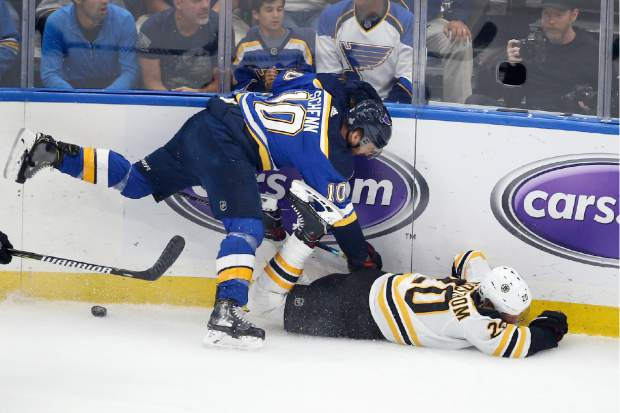 Boston Bruins center Joakim Nordstrom (20), of Sweden, falls as he chases the puck with St. Louis Blues center Brayden Schenn (10) during the first period of Game 6 of the NHL hockey Stanley Cup Final Sunday, June 9, 2019, in St. Louis. (AP Photo/Scott Kane)