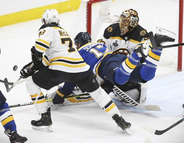 St. Louis Blues left wing Jaden Schwartz (17) falls between Boston Bruins goaltender Tuukka Rask, of Finland, right, and defenseman Charlie McAvoy (73) during the second period of Game 6 of the NHL hockey Stanley Cup Final Sunday, June 9, 2019, in St. Louis. (AP Photo/Scott Kane)