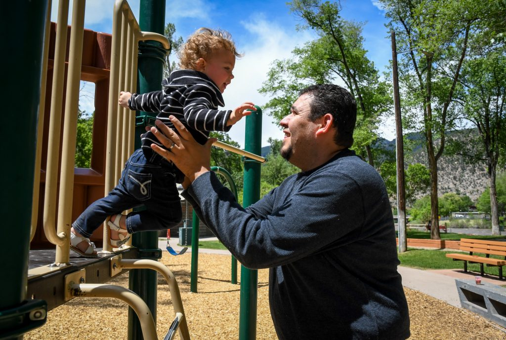 Edgar Niebla catches his 2-year-old adopted daughter Lily at Veltus Park on a sunny afternoon in Glenwood.