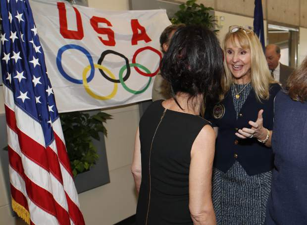 Nancy Hogshead-Makar, back, of Jacksonville, Fla., who won medals in the 1984 Summer Olympics, speaks with Judge Rosemarie Aquilina, who sentenced USA Gymnastics team doctor Larry Nasser to 175 years in prison, after a news conference to announce a plan to introduce legislation aimed at reforming the U.S. Olympic Committee Monday, June 17, 2019, in Denver. Nearly a dozen Olympic athletes were on hand to lend their support to the measure, which U.S. Rep. Diana DeGette, D-Colo., plans to introduce this week. (AP Photo/David Zalubowski)