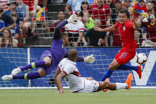 Venezuela forward Jose Salomon Rondon, center, scores against United States goalkeeper Zack Steffen (1) and defender Aaron Long (23) during the first half of an international friendly soccer match, Sunday, June 9, 2019, in Cincinnati. (AP Photo/John Minchillo)