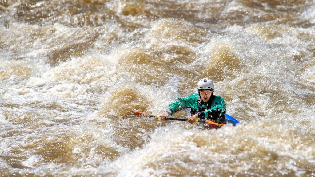 kayaker paddles through turbulant river