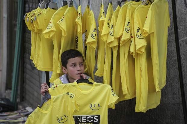 A boy sells yellow jerseys at the main square in the hometown of cyclist Egan Bernal as a crowd gathers to watch on a giant screen the last stage of the Tour de France in Zipaquira, Colombia, Sunday, July 28, 2019. Bernal became the first Colombian to win the cycling's biggest race. (AP Photo/Ivan Valencia)