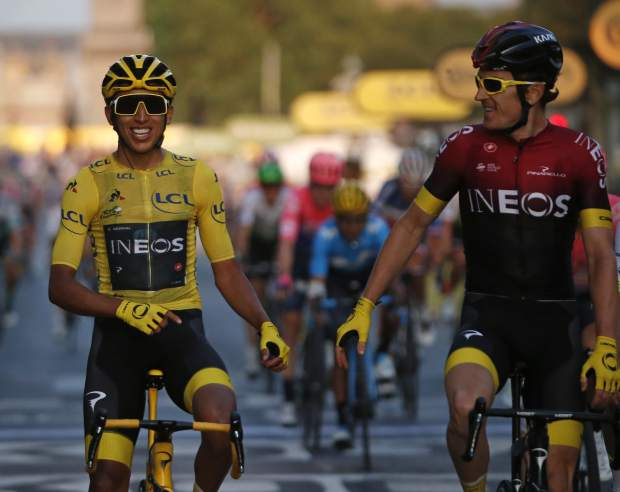 Colombia's Egan Bernal wearing the overall leader's yellow jersey smiles as he crosses the finish line with Britain's Geraint Thomas after winning the Tour de France cycling race over 128 kilometers (79.53 miles) with start in Rambouillet and finish in Paris, France, Sunday, July 28, 2019. (AP Photo/Michel Euler)