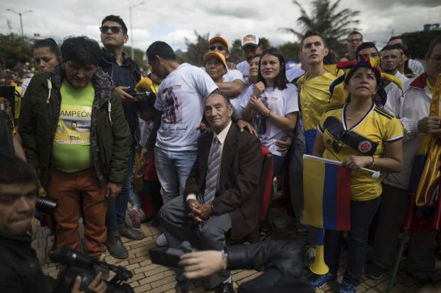 Alvaro Bernal, grandfather of cyclist Egan Bernal, watches a giant screen broadcasting live the final stage of the Tour de France at his hometown in Zipaquira, Colombia, Sunday, July 28, 2019. Bernal became the first Colombian to win the cycling's biggest race. (AP Photo/Ivan Valencia)