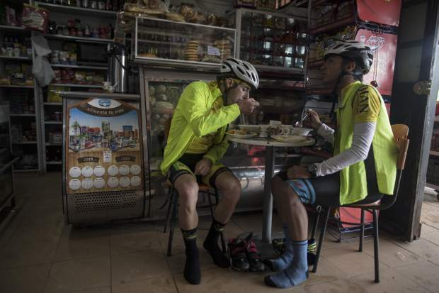 Cyclists have breakfast after a morning ride and before going to the main square of the hometown of cyclist Egan Bernal to watch on a giant screen the final stage of the Tour de France in Zipaquira, Colombia, Sunday, July 28, 2019. Barring a crash or a last-minute health issue Bernal will become the first Colombian to win the cycling's biggest race when the Tour de France ends on Paris' Champs-Elysees on Sunday. (AP Photo/Ivan Valencia)