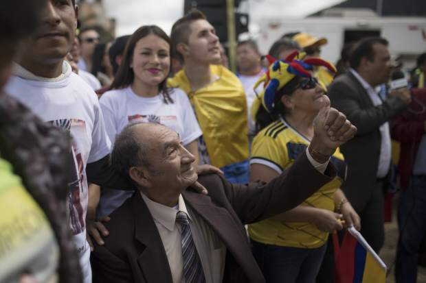 Alvaro Bernal, grandfather of cyclist Egan Bernal, celebrates as he watches a giant screen broadcasting live the final stage of the Tour de France at his hometown in Zipaquira, Colombia, Sunday, July 28, 2019. Bernal became the first Colombian to win the cycling's biggest race. (AP Photo/Ivan Valencia)