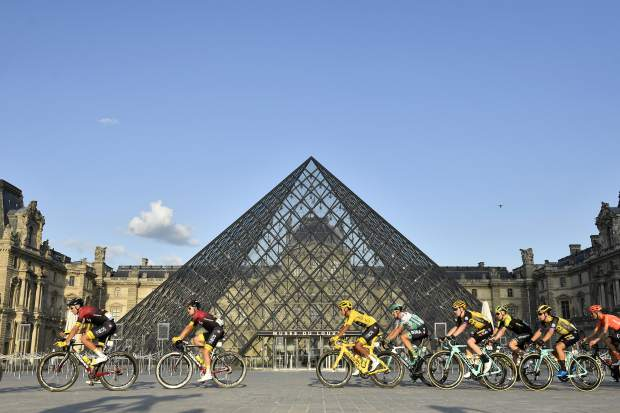 Colombia's Egan Bernal, center, wearing the overall leader's yellow jersey passes-by the pyramid of the Louvre museum with the pack during the 21st and final stage of the Tour de France cycling race over 128km between Rambouillet and the Champs Elysees in Paris, France, Sunday July 28, 2019. (Julien de Rosa/Pool Photo via AP)