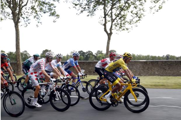 Colombia's Egan Bernal wearing the overall leader's yellow jersey and France's Romain Bardet wearing the best climber's dotted jersey ride in the pack during the twenty-first stage of the Tour de France cycling race over 128 kilometers (79.53miles) with start in Rambouillet and finish in Paris, France, Sunday, July 28, 2019. (AP Photo/Thibault Camus)
