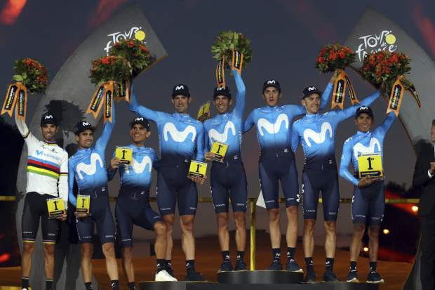 Best team Movistar stand on the podium after the twenty-first stage of the Tour de France cycling race over 128 kilometers (79.53 miles) with start in Rambouillet and finish in Paris, France, Sunday, July 28, 2019. (AP Photo/Thibault Camus)