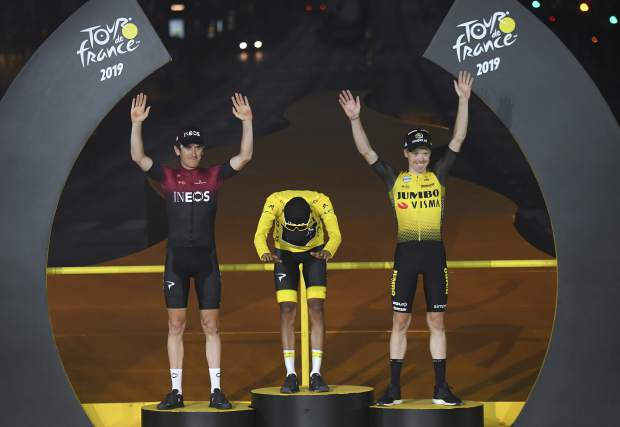 Colombia's Egan Bernal, the winner, center, Britain's Geraint Thomas, who placed second, left, and the Netherlands' Steven Kruijswijk, third, stand on the podium of the Tour de France cycling race in Paris, France, Sunday, July 28, 2019. (Stephane Mantey, Pool Photo via AP)