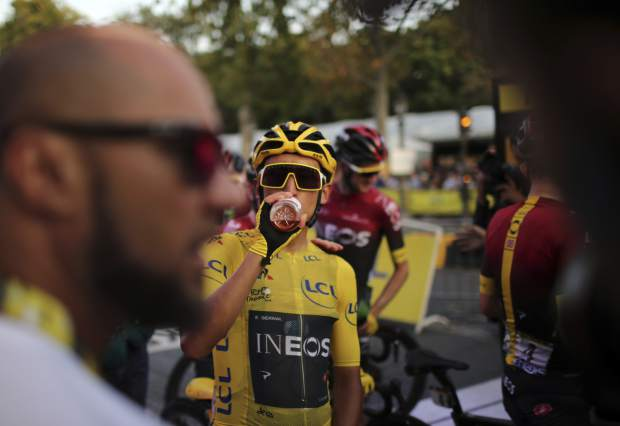 Tour de France winner Colombia's Egan Bernal wearing the overall leader's yellow jersey drinks after the twenty-first stage of the Tour de France cycling race over 128 kilometers (79.53 miles) with start in Rambouillet and finish in Paris, France, Sunday, July 28, 2019. (AP Photo/Thibault Camus)