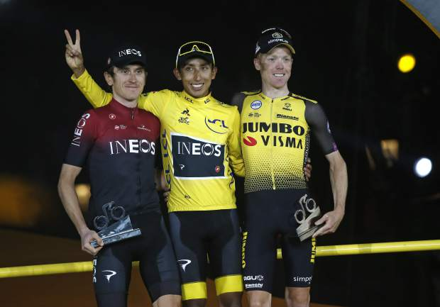 Colombia's Egan Bernal, the winner, center, Britain's Geraint Thomas, who placed second, left, and the Netherlands' Steven Kruijswijk, third, stand on the podium of the Tour de France cycling race in Paris, France, Sunday, July 28, 2019. (AP Photo/Michel Euler)