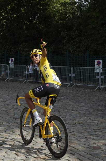 Colombia's Egan Bernal wearing the overall leader's yellow jersey waves as he arrives for the start of the twenty-first stage of the Tour de France cycling race over 128 kilometers (79,53 miles) with start in Rambouillet and finish in Paris, France, Sunday, July 28, 2019. (AP Photo/Thibault Camus)