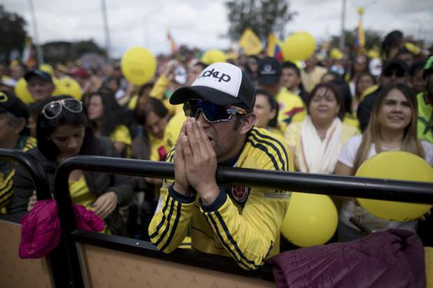 A cycling fan looks at a giant screen broadcasting live the final stage of the Tour de France in the hometown of Colombian cyclist Egan Bernal, in Zipaquira, Colombia, Sunday, July 28, 2019. Bernal became the first Colombian to win the cycling's biggest race. (AP Photo/Ivan Valencia)