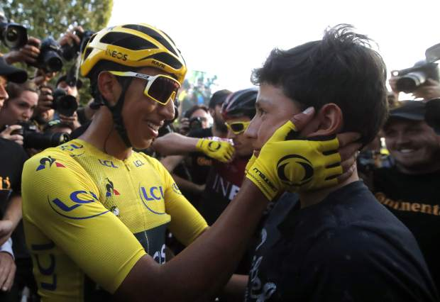 Tour de France winner Colombia's Egan Bernal wearing the overall leader's yellow jersey embraces relative after the twenty-first stage of the Tour de France cycling race over 128 kilometers (79.53 miles) with start in Rambouillet and finish in Paris, France, Sunday, July 28, 2019. (AP Photo/Christophe Ena)
