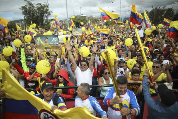 Fans celebrate as they watch a giant screen broadcasting live Egan Bernal winning the final stage of the Tour de France, in his hometown of Zipaquira, Colombia, Sunday, July 28, 2019. Bernal became the first Colombian cyclist to win the cycling's biggest race. (AP Photo/Ivan Valencia)