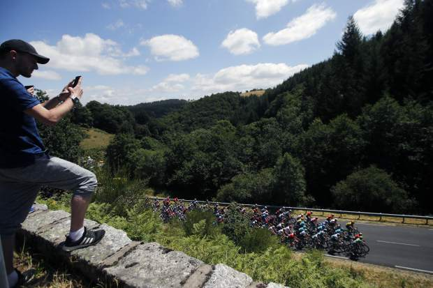 France's Julian Alaphilippe wears the overall leader's yellow jersey on the podium after the tenth stage of the Tour de France cycling race over 217 kilometers (135 miles) with start in Saint-Flour and finish in Albi, France, Monday, July 15, 2019. (AP Photo/ Christophe Ena)