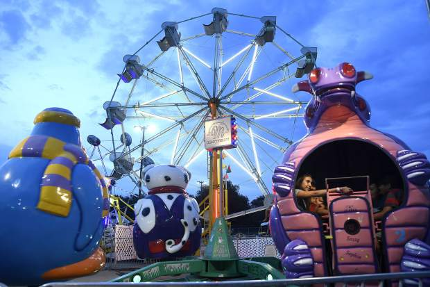 The carnival lights up the early evening sky at the 80th edition of the annual Garfield County Fair last year in Rifle.