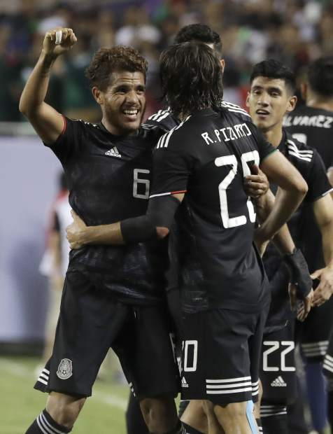 Mexico midfielder Jonathan Dos Santos (6) celebrates with forward Rodolfo Pizarro (20) after scoring his first goal against the United States during the second half of the CONCACAF Gold Cup final soccer match in Chicago, Sunday, July 7, 2019. (AP Photo/Nam Y. Huh)