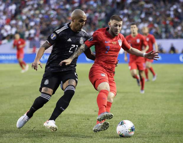 United States forward Paul Arriola, right, controls the ball against Mexico defender Luis Rodriguez during the first half of the CONCACAF Gold Cup final soccer match at Soldier Field in Chicago, Sunday, July 7, 2019. (AP Photo/Nam Y. Huh)