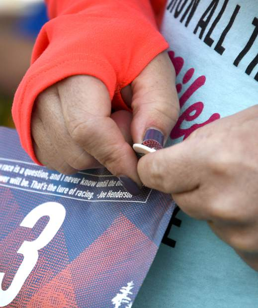 Domenica Smith, a participants in the 2019 Hogback Hustle pins her number on before the start of race Saturday at City Market in New Castle. The 5k run and walk is the fifth of six races in the Colorado River Valley Charity Races Series.