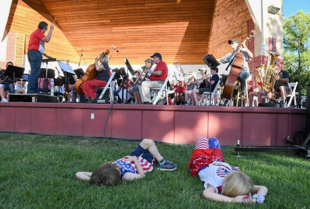 Two young kids lay back and enjoy music by Symphony in the Valley at the Glenwood Springs 4th of July Celebration at Two Rivers Park on Thursday afternoon.