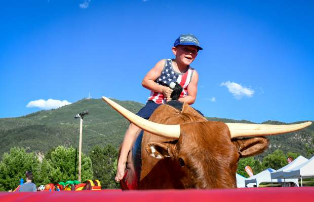 Five-year-old Camden Windschell hangs on for dear life while riding the mechanical bull at the Glenwood Springs 4th of July Celebration at Two Rivers Park on Thursday afternoon.