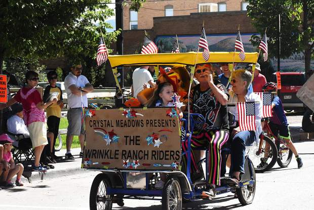 Lee Dudley steers the pedal cart for the Crystal Meadows Senior Housing residents in the Carbondale 4th of July