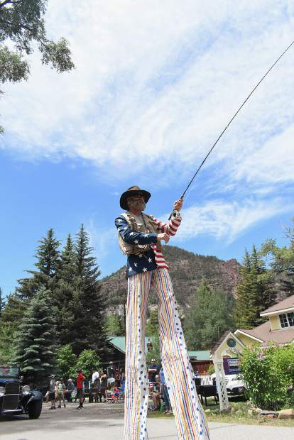 Kayo Ogilby was up on stilts with his fly rod casting for a couple of fish hats worn by his daughters Laia and Amelie during the Redstone 4th of July Parade on Thursday.
