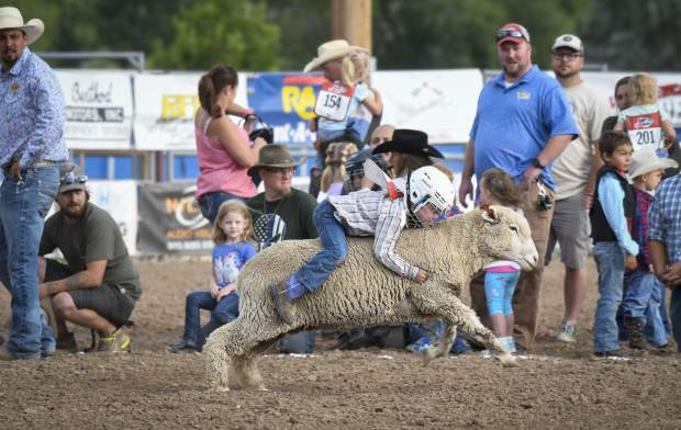 Family and friends keep a close watch as a contestant in Monday night's Mutton Bustin' streaks across the arena floor aboard a sheep.