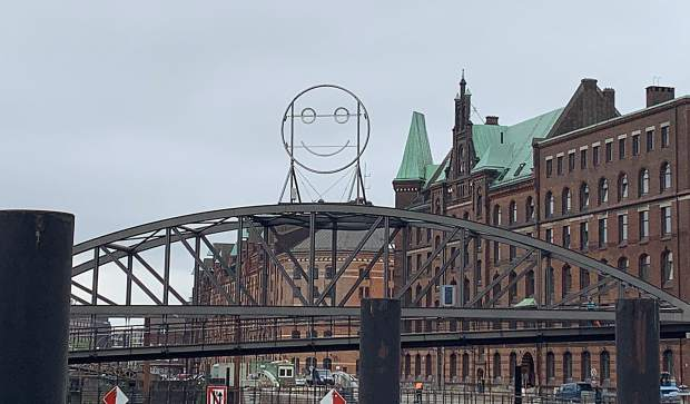 A bridge with a smiley face sculpture over one of the canals in Speicherstadt, the warehouse district of Hamburg, Germany.