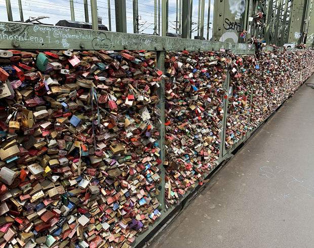 Love locks on the main rail bridge that crosses the Rhine River in the Altstadt-Nord section of Cologne, Germany.