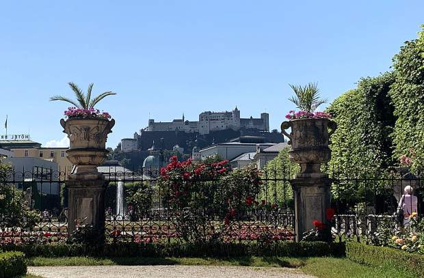 View of the hilltop Hohensalzburg Fortress from a garden in the historic Salzburg City Center.