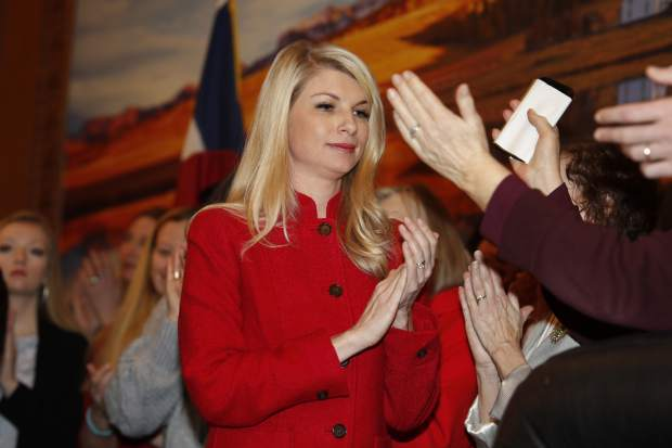 FILE - In this April 12, 2019, file photo, Colorado State Sen. Brittany Pettersen, D-Lakewood, applauds after speaking at a bill signing that allowed Colorado to become the 15th state to adopt a