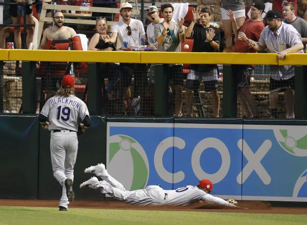 Colorado Rockies center fielder Ian Desmond, right, and Charlie Blackmon (19) cannot make the play on a ground-rule double hit by Arizona Diamondbacks' Christian Walker in the first inning during a baseball game, Saturday, July 6, 2019, in Phoenix. (AP Photo/Rick Scuteri)
