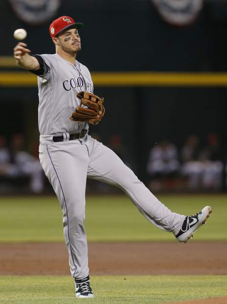 Colorado Rockies third baseman Nolan Arenado makes the off balance throw for an out on a ball hit by Arizona Diamondbacks' Christian Walker in the first inning during a baseball game, Sunday, July 7, 2019, in Phoenix. (AP Photo/Rick Scuteri)