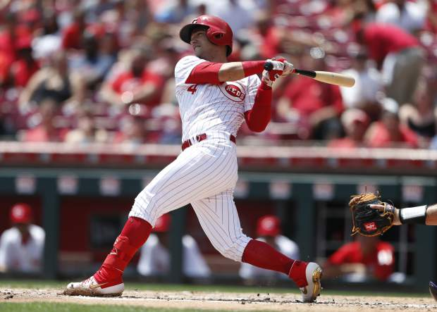 Cincinnati Reds' Jose Iglesias hits an RBI-single off Colorado Rockies starting pitcher Peter Lambert during the second inning of a baseball game, Sunday, July 28, 2019, in Cincinnati. (AP Photo/Gary Landers)