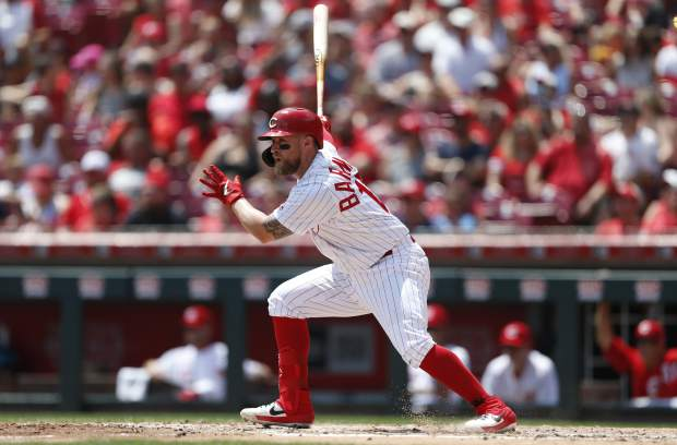 Cincinnati Reds' Tucker Barnhart follows through on an RBI-single off Colorado Rockies starting pitcher Peter Lambert during the second inning of a baseball game, Sunday, July 28, 2019, in Cincinnati. (AP Photo/Gary Landers)
