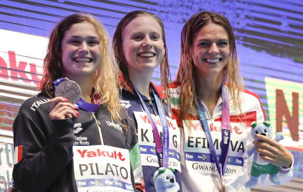Gold medalist United States' Lilly King, centre, stands with silver medalist Italy's Benedetta Pilato, left, and bronze medalist Russia's Yuliya Efimova following the women's 50m breaststroke final at the World Swimming Championships in Gwangju, South Korea, Sunday, July 28, 2019. (AP Photo/Lee Jin-man)