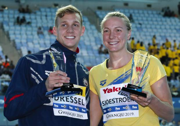 United States' Caeleb Dressel, left, and Sweden's Sarah Sjsotrom pose with their trophies for top male and female swimmers at the World Swimming Championships in Gwangju, South Korea, Sunday, July 28, 2019. (AP Photo/Lee Jin-man)