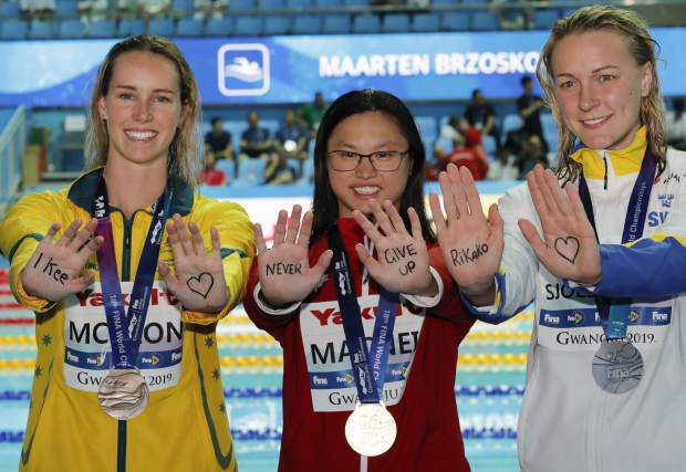 Gold medalist Canada's Margaret MacNeil, centre, gestures with silver medalist Sweden's Sarah Sjostrom, right, and bronze medalist Australia's Emma McKeon to Japanese swimmer Rikako Ikee following the medal ceremony for the women's 100m butterfly final at the World Swimming Championships in Gwangju, South Korea, Monday, July 22, 2019. (AP Photo/Lee Jin-man)