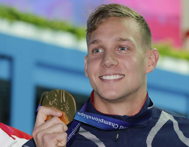 Gold medalist United States' Caeleb Dressel hold sup his medal after winning the men's 50m butterfly final at the World Swimming Championships in Gwangju, South Korea, Monday, July 22, 2019. (AP Photo/Lee Jin-man)