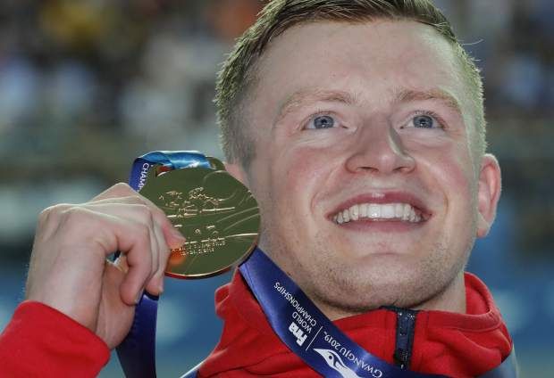 Britain's Adam Peaty holds up his gold medal after winning the men's 100m breaststroke final at the World Swimming Championships in Gwangju, South Korea, Monday, July 22, 2019. (AP Photo/Lee Jin-man)