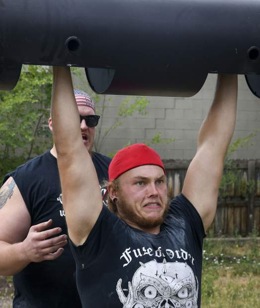With a spot from Greg Orosz,  Jesse DuPlesys lifts the log bar as they prepare for the annual Strongman event at the Garfield County Fairground next week in Rifle.