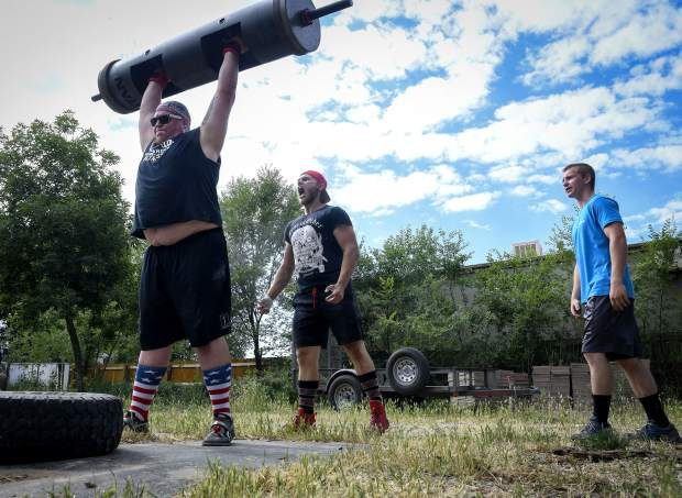 Greg Orosz lifts the log bar as training partners Jesse DuPlesys and Jo Ritter offer encouragment as they go through practice at Orosz's Silt home as they prepare for the annual Strongman event at the Garfield County Fairground next week in Rifle.