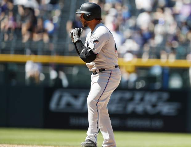 Miami Marlins' Harold Ramirez gestures to the dugout after his RBI-double off Colorado Rockies starting pitcher Peter Lambert in the sixth inning of a baseball game Sunday, Aug. 18, 2019, in Denver. (AP Photo/David Zalubowski)