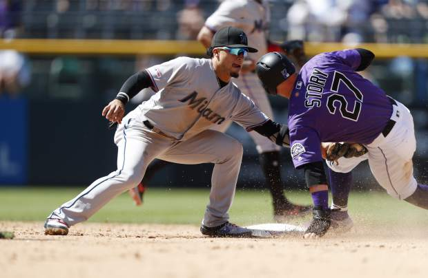 Miami Marlins second baseman Isan Diaz, left, tags out Colorado Rockies' Trevor Story as he tries to steal second base in the sixth inning of a baseball game Sunday, Aug. 18, 2019, in Denver. (AP Photo/David Zalubowski)